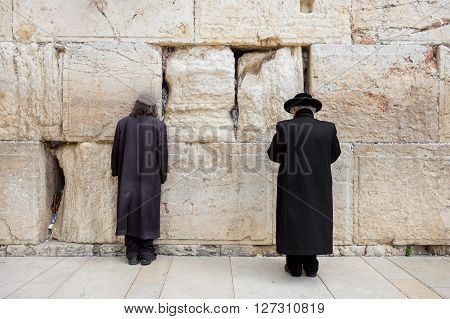 JERUSALEM ISRAEL - MARCH 15 2016: Two men praying at the men's section of the Wailing (Western) Wall in the old town Jerusalem (Israel)