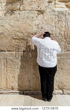 JERUSALEM ISRAEL - MARCH 15 2016: Man praying at the men's section of the Wailing (Western) Wall in the old town Jerusalem (Israel)