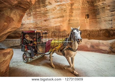 PETRA JORDAN - MARCH 17 2016: Three bedouins riding a horse cab through the canyon in the ancient city of Petra