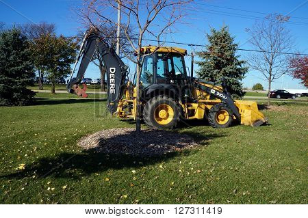 NAPERVILLE, ILLINOIS / UNITED STATES - NOVEMBER 3, 2015: A John Deere 310SJ backhoe sits parked in the Naperville Park District's Wildflower Park.