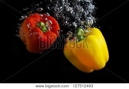 Fresh paprika splash in water with air bubbles. Red and yellow paprika in water on black background. Healthy food. Wash vegetables.