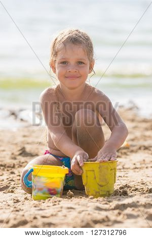 Glad Kid Playing On A Sandy Beach With A Pond And Sand Molds