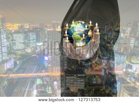 Business man holding the small world in his hands with cityscape (Elements of this image furnished by NASA)