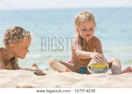 Two Girls On The Beach On A Sunny Day, Playing With Sand And A Bucket On A Background Of The Sea