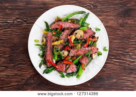 Grilled steak with stir-fried vegetables on plate