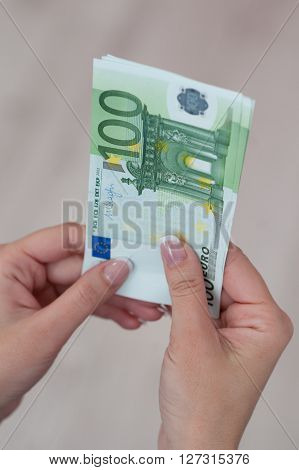 Famale hand holding several euro money banknotes. ** Note: Shallow depth of field