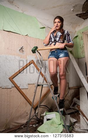 Beautiful sexy woman with sledge hammer is frightened after attempt to hang up frame for picture