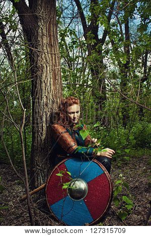 Redhead beautiful scandinavian woman sitting in a forest with weapons and shield