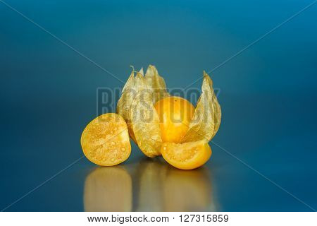 Colorful ground cherry with blue background and reflexion Physalis fruit
