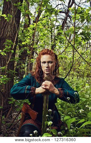 Redhead beautiful scandinavian girl posing in a forest with sword
