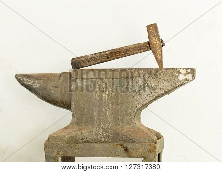 Old hammer and anvil tools against white clay wall as a background.