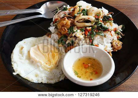Rice topped with spicy fried squid basil leaves and fried egg (Thai food)