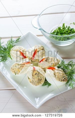 Dish with hard boiled eggs in mayonnaise parsley nad chopped chives on white plank background