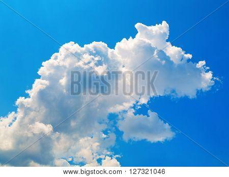 Bright blue sky with white cumulus cloud.