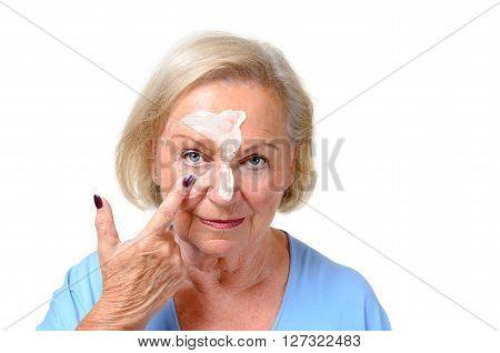 Attractive Blond Senior Lady Applying Cosmetics