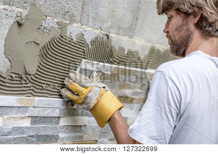 Closeup of young man with a beard precisely placing an ornamental tile on a wall covered with glue.