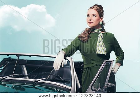 Retro 1960 woman standing in open door of convertible car.