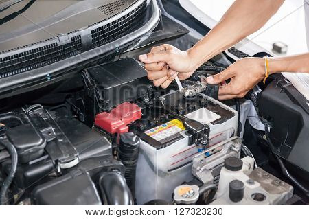 Mechanic Engineer Fixing Car Battery In Garage (selective Focus)
