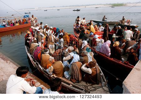VARANASI, INDIA - JANUARY 2, 2013: A lot of people sit on the crowded boats to cross the Ganges River on January 2, 2013. The 2525 km river rises in the western Himalayas flows through the Gangetic Plain