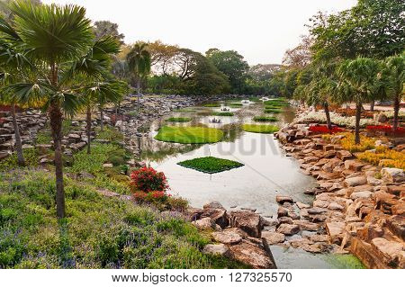 Nong Nooch Tropical Garden in Pattaya Thailand. Beautiful pond with palm trees.