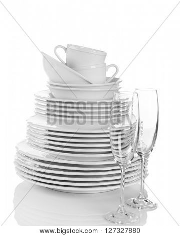 Stacked white clean plates, glasses and cups isolated on white