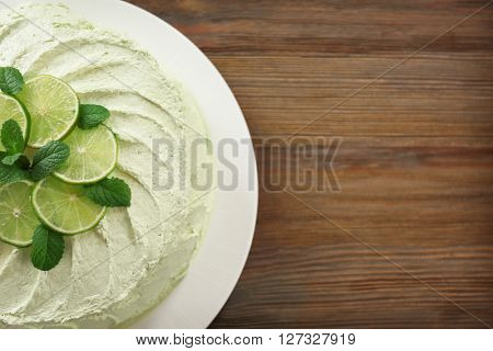 Delicious creamy lime cake on wooden table, top view