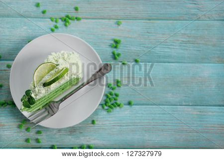 Piece of delicious creamy lime cake on wooden table, top view