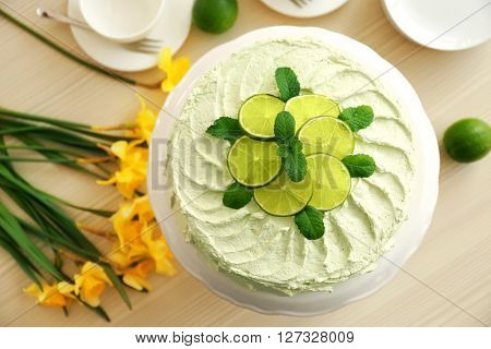 Lime cake and bouquet of yellow daffodils.