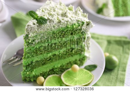 Piece of delicious creamy lime cake on saucer closeup