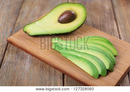 Slices of fresh avocado on wooden background