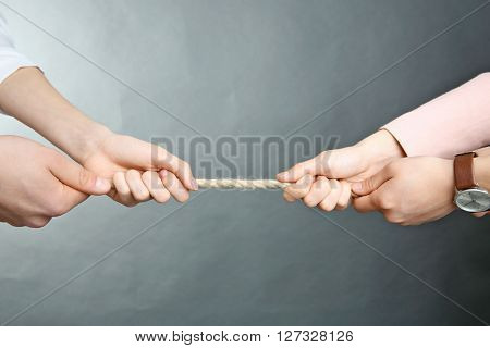 People hands pulling rope for playing tug of war on grey background
