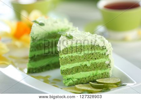 Pieces of delicious creamy lime cake on white plate closeup