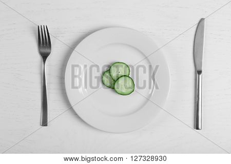 Pieces of cucumber in a white plate on white table. Top view.