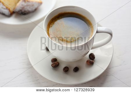 Cup of coffee with cake on light wooden background