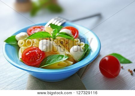Cooked penne pasta with mozzarella, fresh tomatoes and basil in blue plate on wooden table