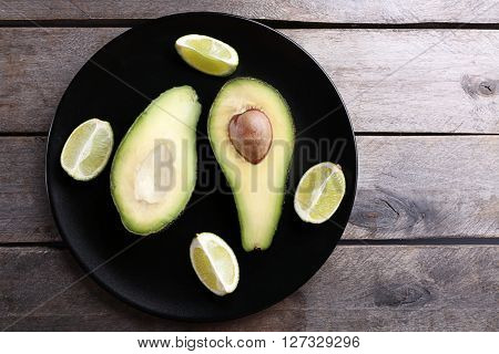 Sliced avocado with lime on black plate