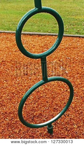 Wet green playground rings positioned in front of wood chips and grass.