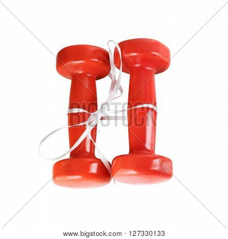 Two red dumbbell. Red dumbbells tied with satin ribbon. Isolated with clipping path on white background. Top view.