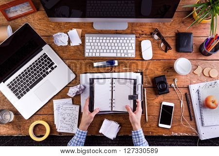 Business person at office desk holding a personal organizer.  Smart phone, camera, computer and various office supplies around the workplace.