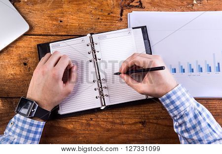 Hands of unrecognizable businessman writing into personal organizer. Chart graph, wooden background.