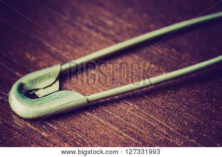 a safety pin on a wooden background