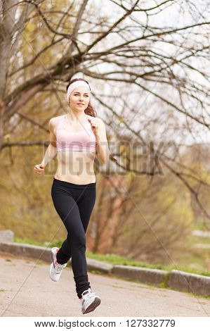 Young Happy Woman Jogging In The Spring Park