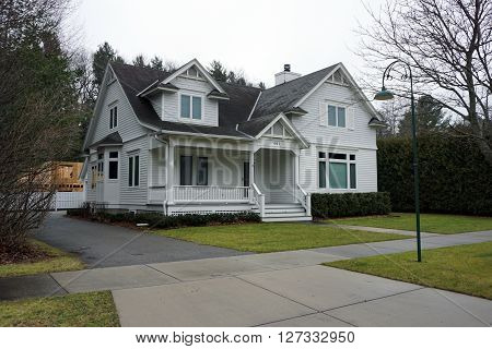 HARBOR SPRINGS, MICHIGAN / UNITED STATES - DECEMBER 23, 2015: A white home with a front porch on Second Street in Harbor Springs.