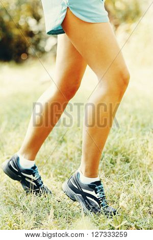 Runner feet on grass closeup. Retro style