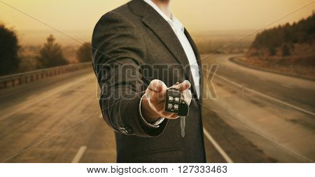 Businessman holding car key on bright background
