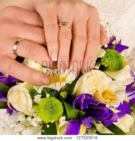 a wedding hands with rings and bouquet