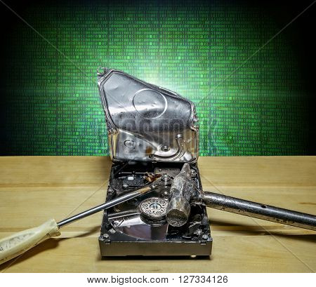 Opened and broken the hard drive from the computer in the background of the digits of the matrix