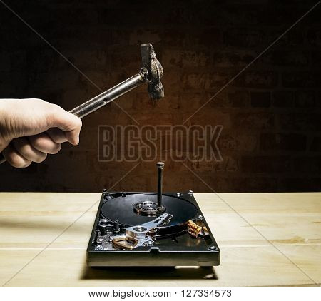 A hammer hits a nail into the hard drive from the computer against a brick wall