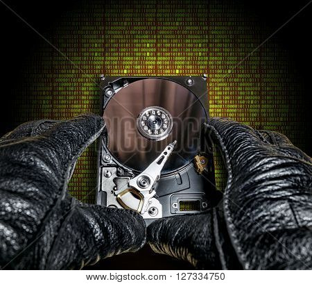 the hard drive from the computer in the hands in gloves on a background of digits of the matrix