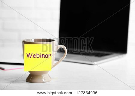 A cup with sticky note on the office table, close up. Webinar concept